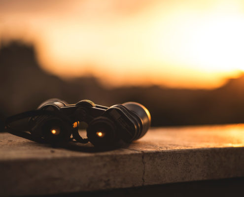 Success Leaves Clues binoculars and sunset